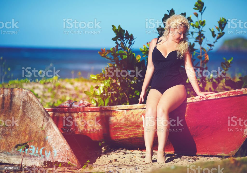 plus size young woman sitting on the boat on sunny beach stock photo