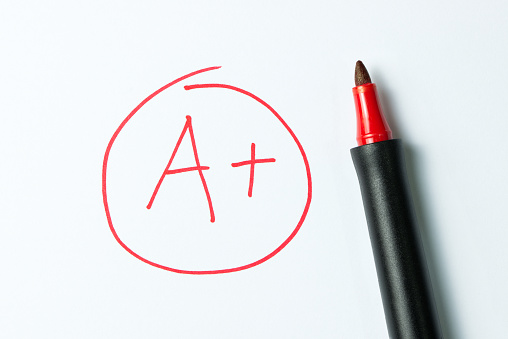 A plus grade written in red, on notebook paper with the pen sitting there.