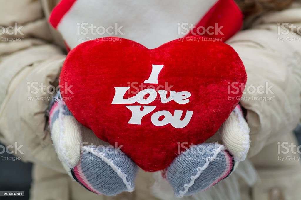 Plush heart in the hands of wearing knitted mittens stock photo