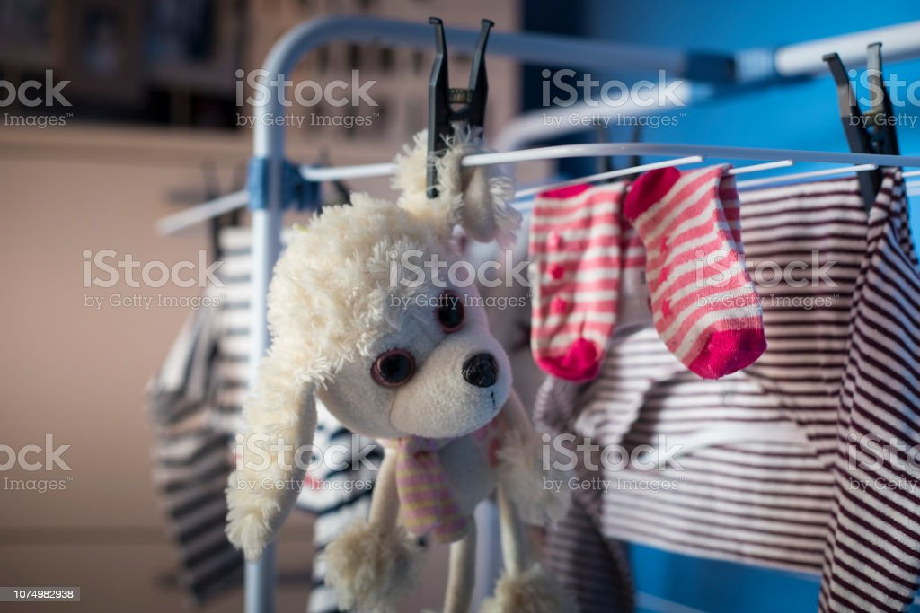white dog plush toy hanging dry with laundry clothes after being...
