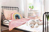 Plush toy, rainbow pillow and pink blanket on kid's bed in white bedroom interior. Real photo