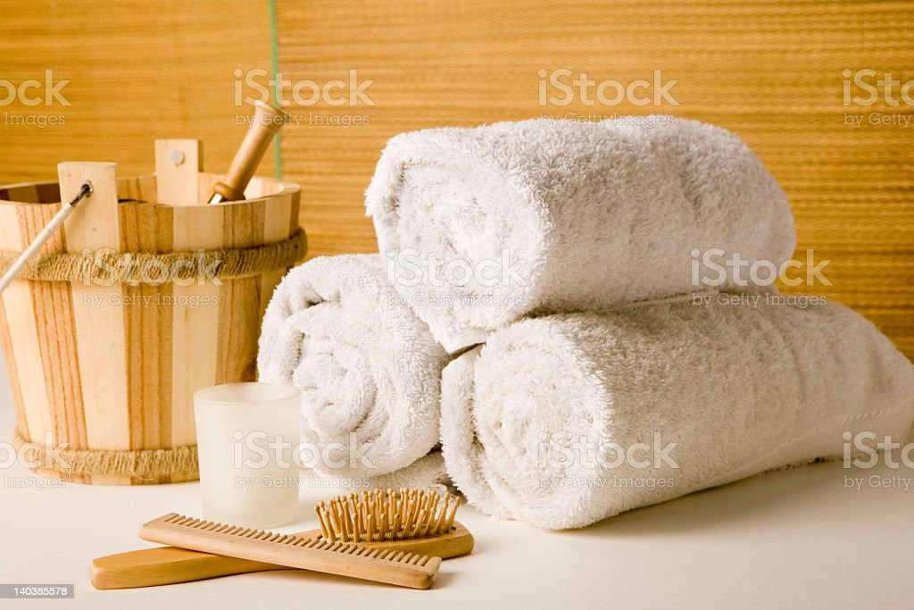 Plush white towels, wooden brush, comb, and candle at a spa royalty-free stock photo