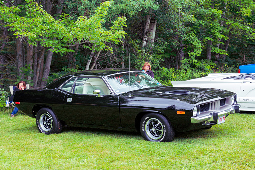Moncton, New Brunswick, Canada - July 9, 2016 : 1974 Plymouth Cuda parked in Centennial Park during 2016 Atlantic Nationals, Moncton, New Brunswick, Canada. A woman sits in a lawn chair behind the car while another woman stands near to the car's driver side.