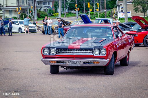 Truro, Nova Scotia, Canada - July 14, 2019 : 1969 Plymouth Roadrunner muscle car at Annual Blaikies Mopar Show & Shine. Behind the classic muscle car, people walk among the vintage cars.