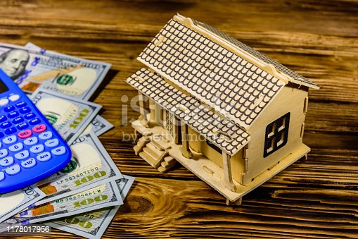 Plywood model of house, calculator and one hundred dollar banknotes. Loan, real estate concept
