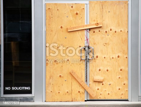 Boarded up doors of business closed with lock and chain