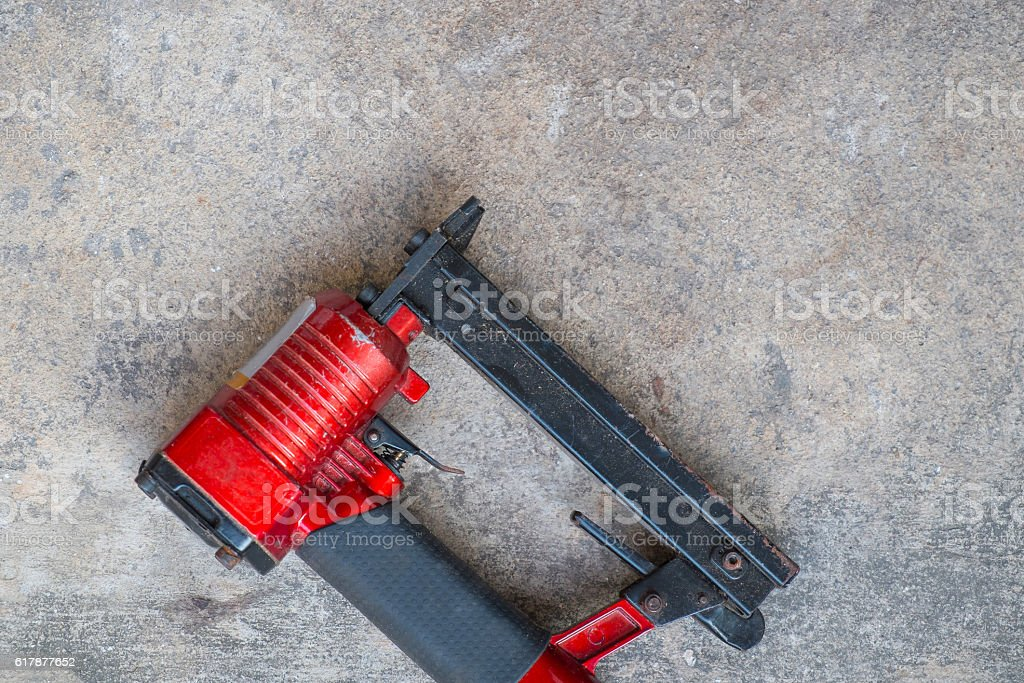 pneumatic staples on cement background, handpiece of airgun stock photo