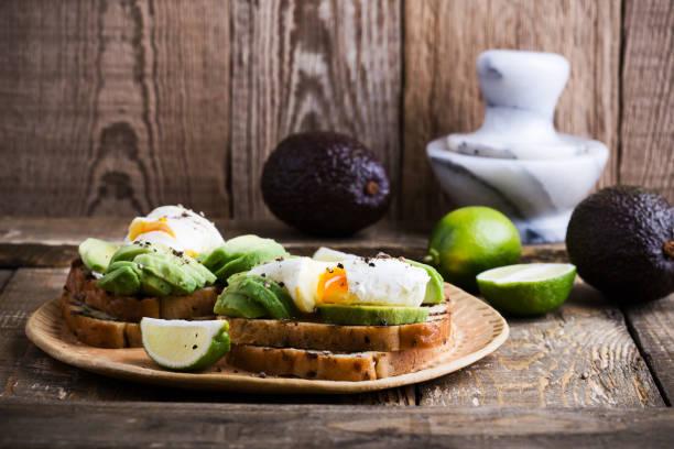 Pochiertes Ei und geschnittene Avocado auf Vollkornbrot Toastbrot – Foto