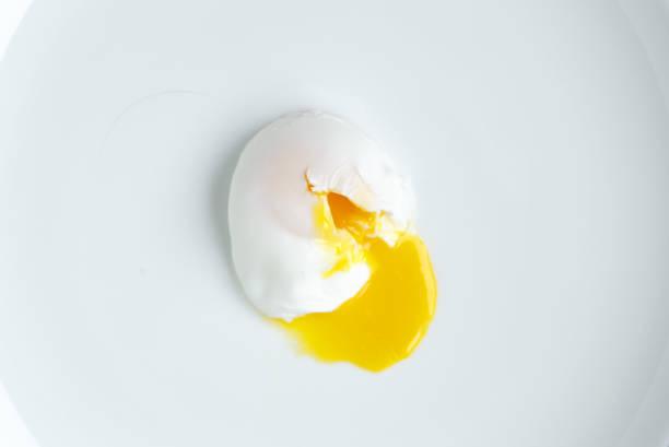 poached egg closeup shot on white background stock photo