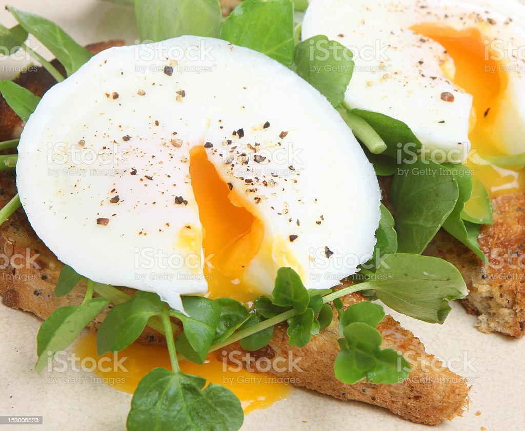 Poached egg cracked open over greens and toast royalty-free stock photo