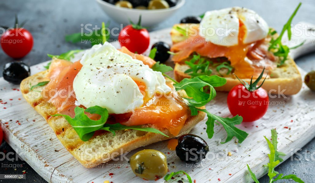 Poached egg on grilled toast with smoked salmon, rucola, olives and vegetables on white board. healthy breakfast stock photo