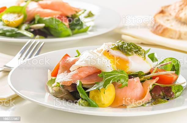 Escalfado Huevo Una Ensalada De Salmón Ahumado Tomates Cherry Y Pesto Foto de stock y más banco de imágenes de Albahaca