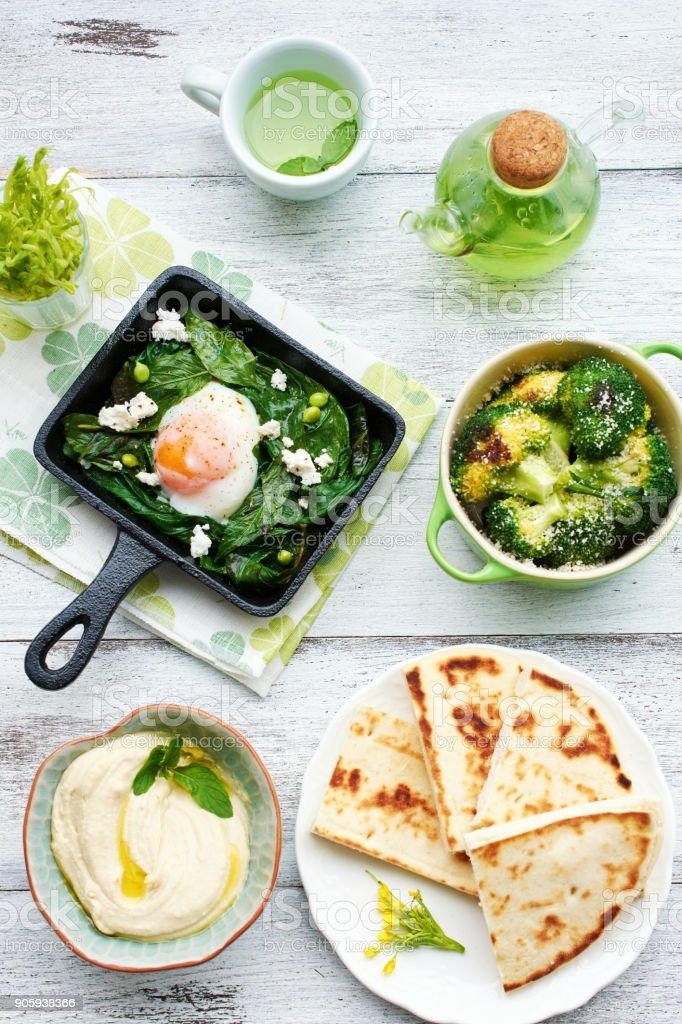Pochiertes Ei mit Spinat, Basilikum und Feta in einer Pfanne gebacken, Brokkoli, Hummus, Fladenbrot und grüner Tee auf weißen Tisch. – Foto
