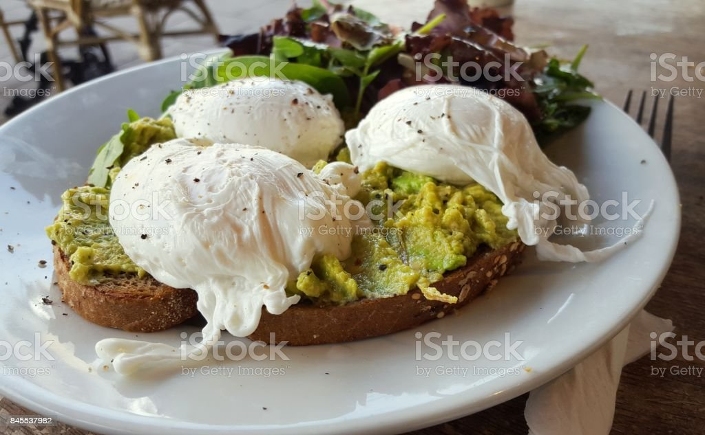 Poached eggs and avocado on toast at a London cafe stock photo