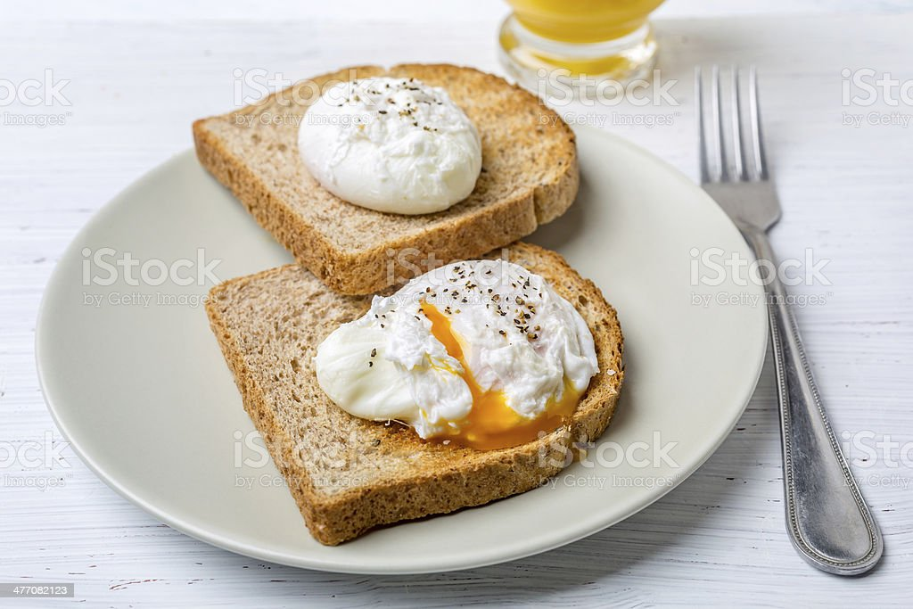 Poached Eggs on Whole Grain Bread Toasts stock photo