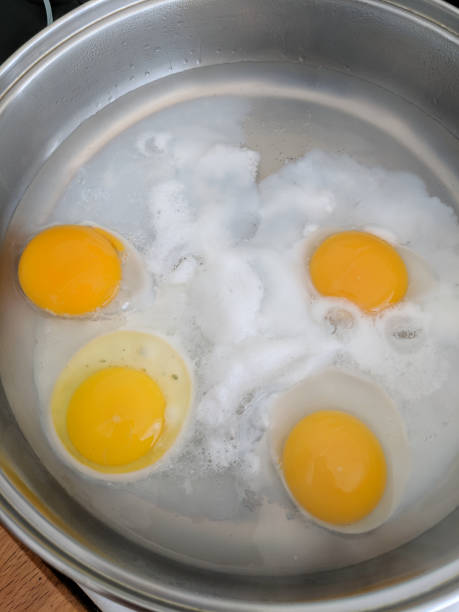 Poaching fresh eggs in a pan of water. stock photo