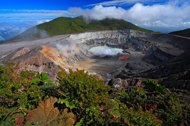 Poas volcano in Costa Rica. Volcano landscape from Costa Rica. Active volcano with blue sky with clouds. Hot lake in the crater Poas. Volcano in Costa Rica. The crater and the lake of the hill Arenal. stock photo