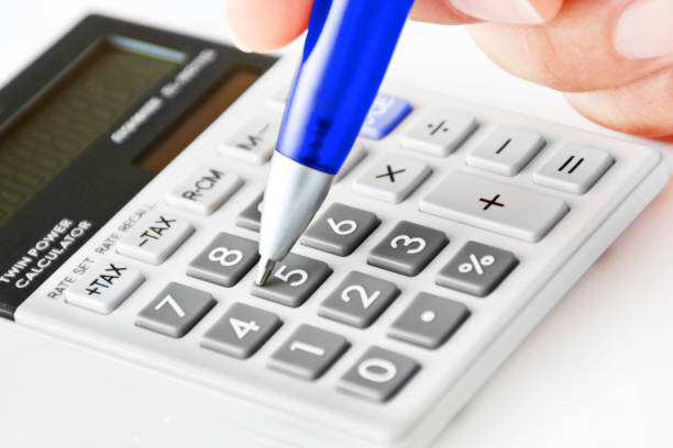 Pocket calculator with hand and blue ballpoint pen close-up background stock photo