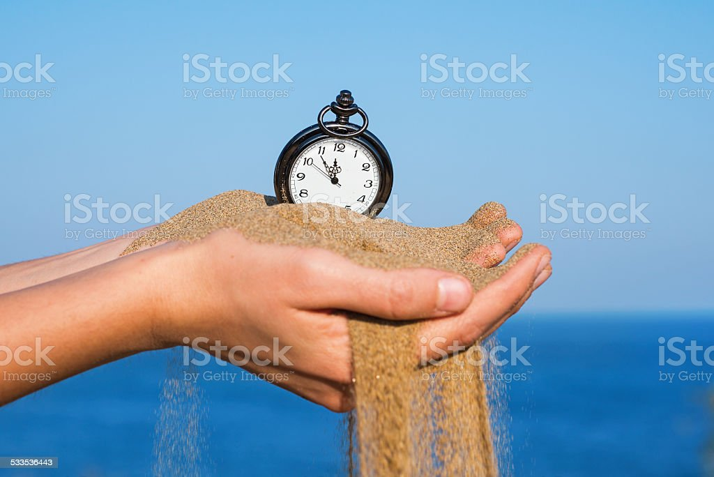 pocket clock in hands and sand flowing stock photo