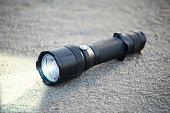pocket LED flashlight lies on a sand