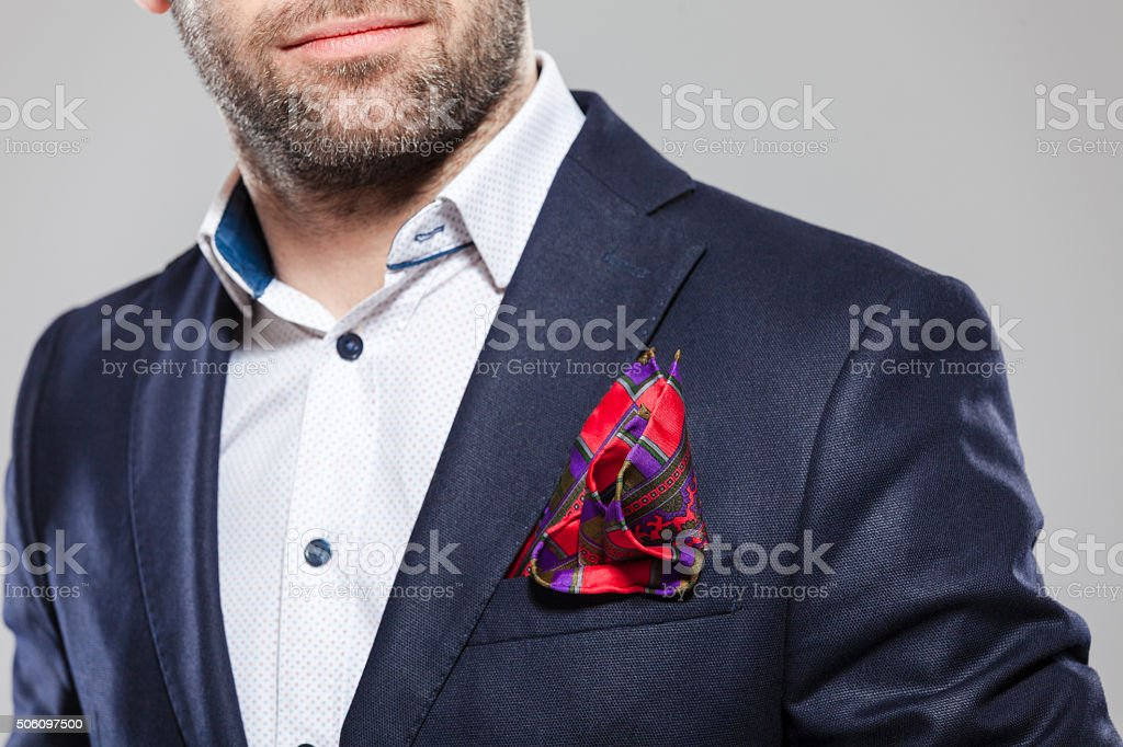 Pocket square Close up of bearded busienssman wearing white shirt, navy blue jacket and pocket square. Unrecognizable person, part of.  Adult Stock Photo