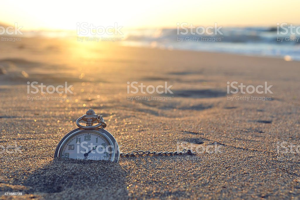 Pocket watch nestled in the sand of a beach at sunset stock photo