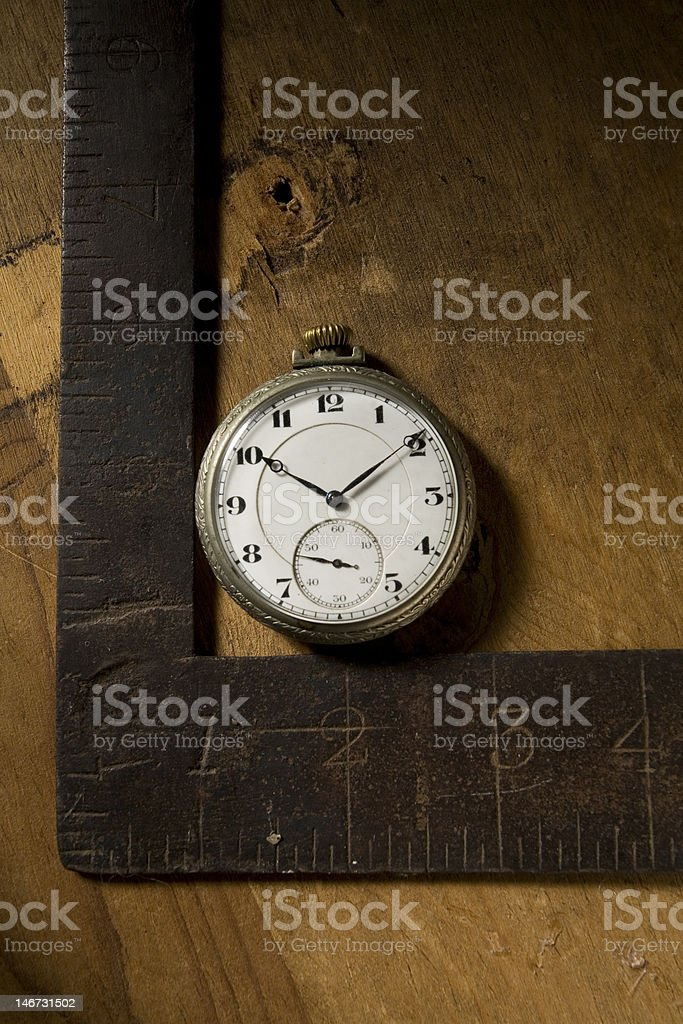Pocket Watch next to antique measuring device stock photo
