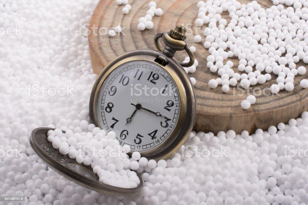 Pocket watch on white polystyrene foam balls stock photo