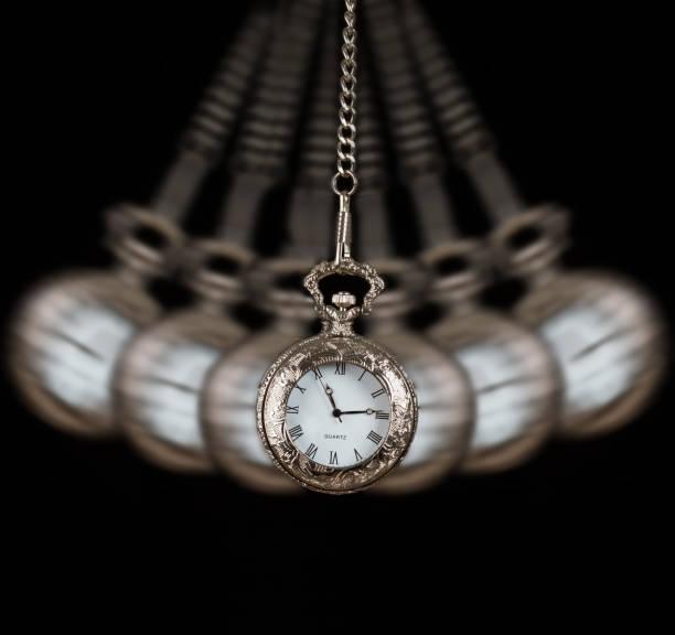 argent de montre de poche se balançant sur un fond noir chaîne d'hypnotiser - pendule photos et images de collection
