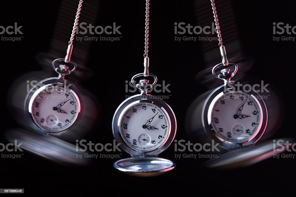 Pocket watch swinging on a chain to hypnotise stock photo