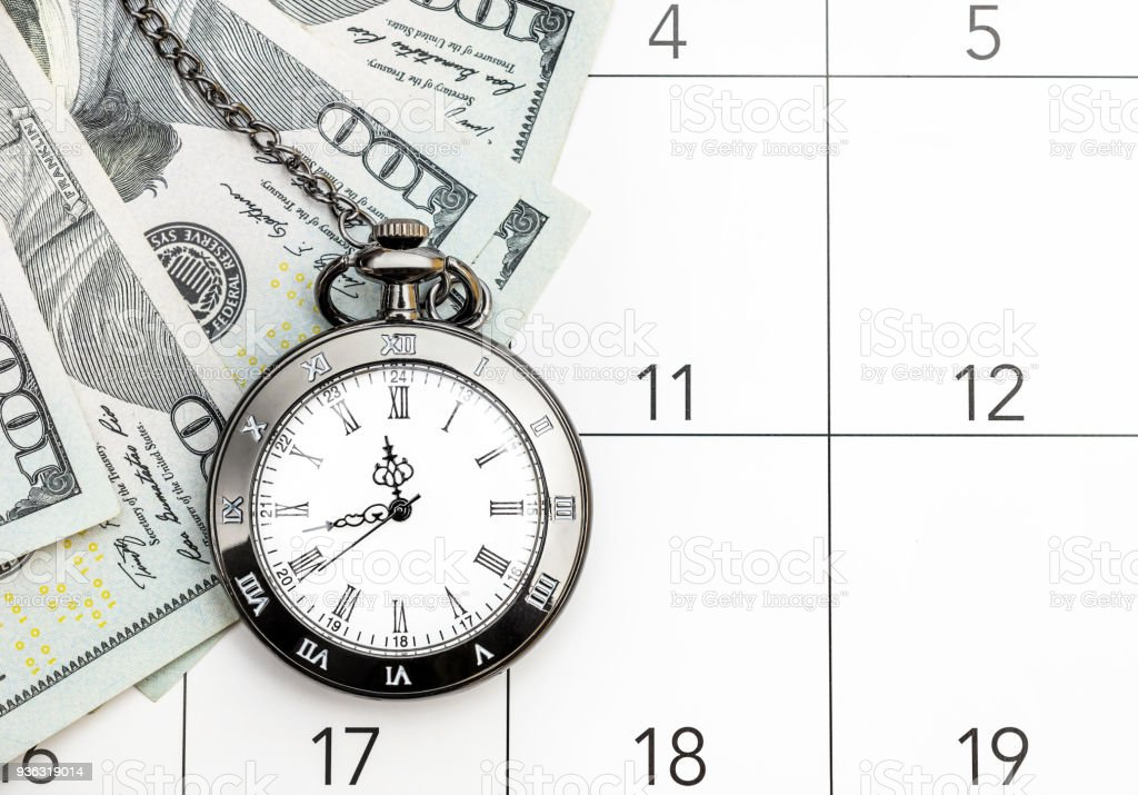 Pocket watch with money on the calendar. Time is money.
