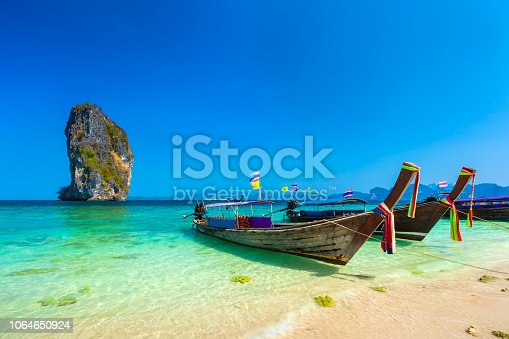 Wooden longtailed boats on a sandy beach in the crystal clear turquoise water of the Adaman Sea near the picturesque limestone rock island under a blue sky.