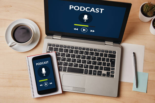 Podcast concept on laptop and smartphone screen over wooden table stock photo