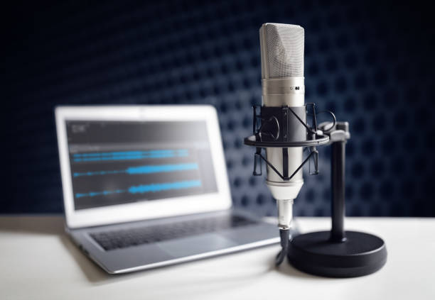 Podcast microphone and laptop computer in recording studio stock photo