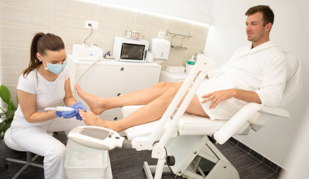 Podiatrist using special grinding equipment and making procedure polish Podiatrist using special grinding equipment and making procedure polish on male patient pedicure manicure men beauty spa stock pictures, royalty-free photos & images