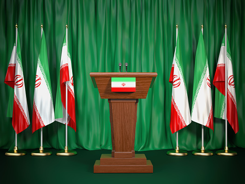 istock Podium speaker tribune with Iran flags. Briefing of president of Iran. Politics concept. 983346860