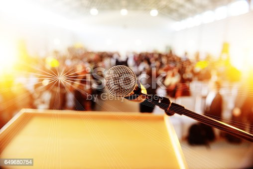 istock Podium with microphone infront of people seated 649680754