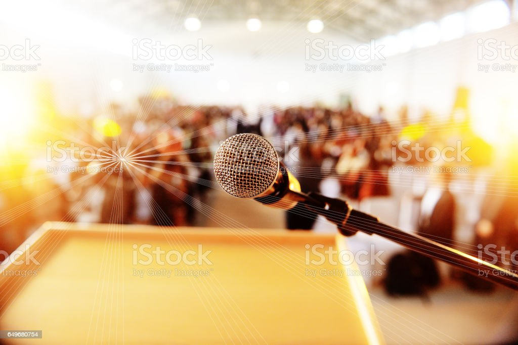 Podium with microphone infront of people seated stock photo