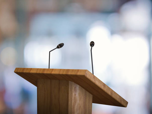 podium with microphone 3d rendering wooden podium with microphone on blurred background speech stock pictures, royalty-free photos & images