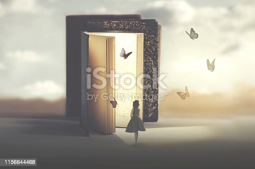 istock poetic encounter between a woman and butterflies coming out of a book 1156644468