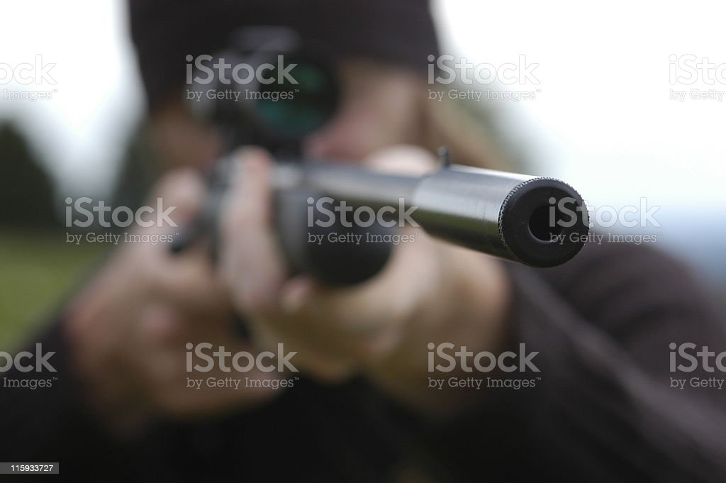 Point and shoot Hunter aiming through the scope of his rifle. Accuracy Stock Photo