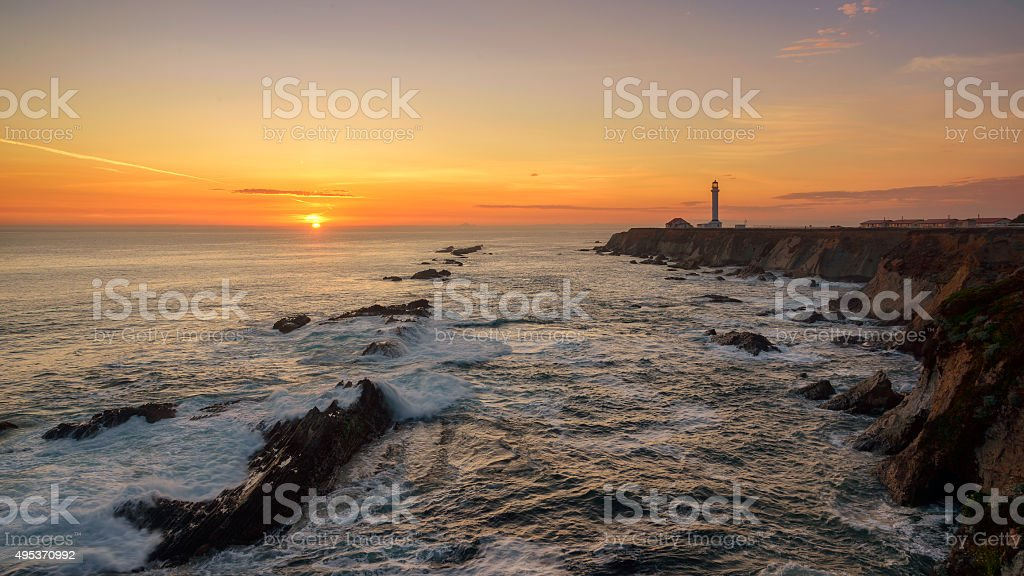Point Arena Lighthouse with splashing surf at sunset, Pacific Ocean stock photo