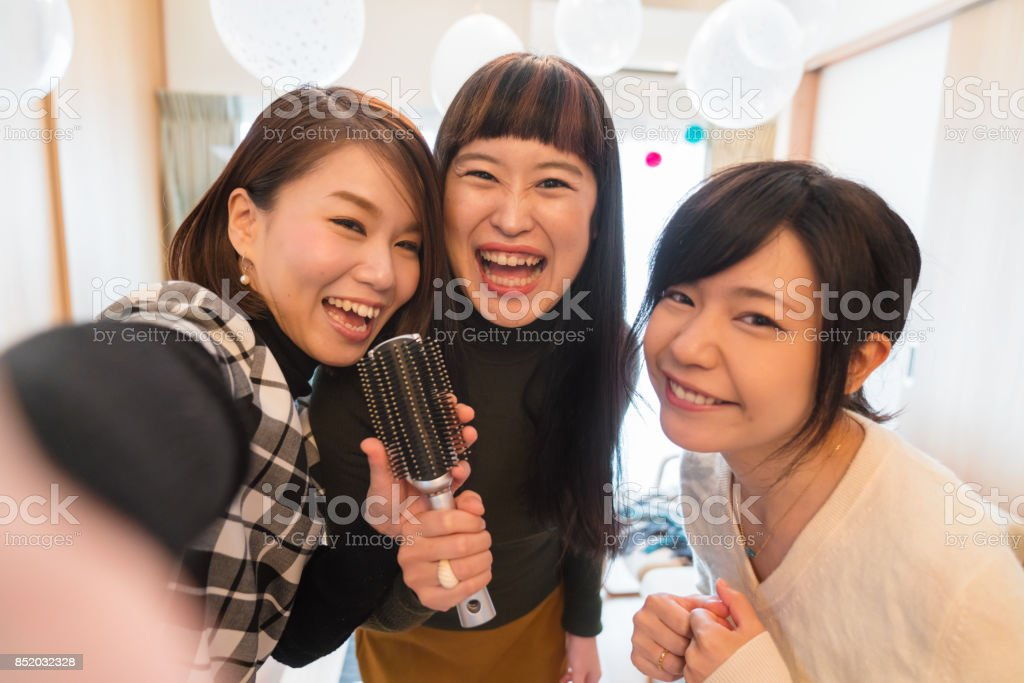 Point of view as three young women take a selfie whilst singing Karaoke at home using a hair brush at Christmas stock photo