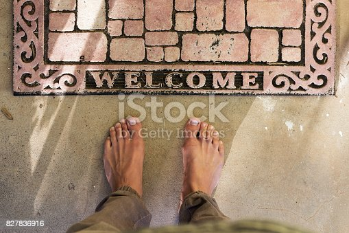 Point of view of bare feet at home front door welcome mat on concrete patio.