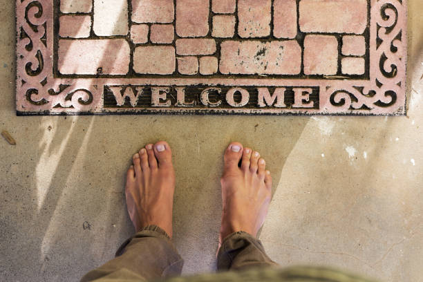 Point Of View Bare Feet At Home Welcome Door Mat stock photo