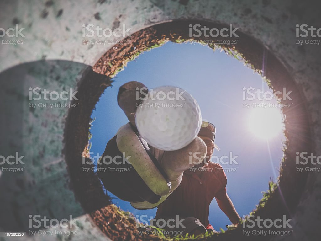 Point Of View Golf Player and Ball From Inside Hole stock photo