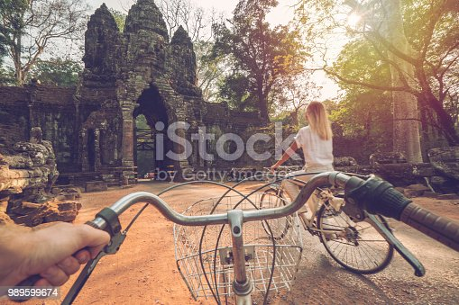 Personal perspective of cheerful young couple cycling in the country side of Cambodia, Siem Reap. People travel recreational activities concept