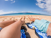 Point of view of couple's feet on beach, relaxing and sunbathing, Maui, Hawaii, USA