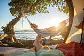 Point of view of man's feet from inside a tent camping on the beach in Hawaii looking at girlfriend in hammock outdoors