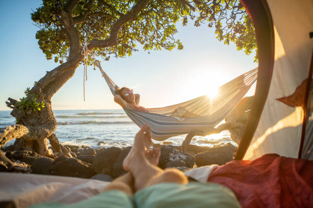 Point of view of man's feet from inside a tent camping on the beach in Hawaii looking at girlfriend in hammock outdoors stock photo